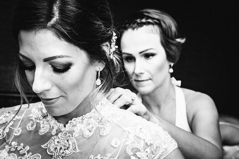 Bridesmaid helping bride into dress
